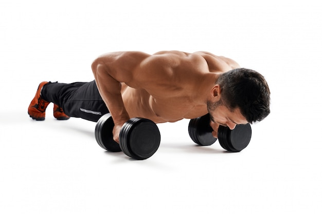 Muscular man doing push ups using dumbbells.