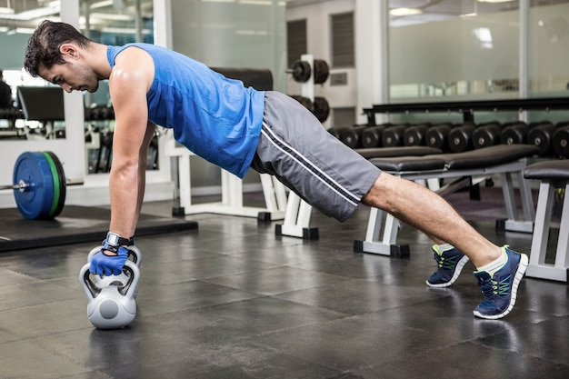 Muscular man doing push ups with kettlebells at the gym