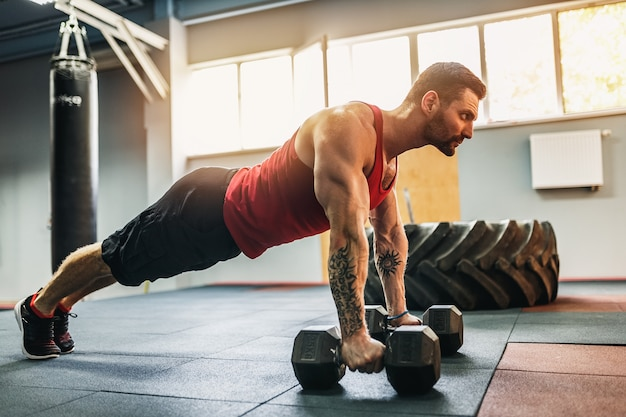 Muscular man doing pushup exercise with dumbbell