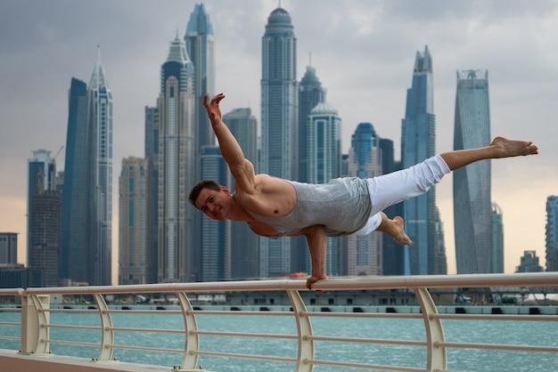 ドバイの高層ビルの街並みと路上でトレーニングをしている筋肉質の男。健康的なライフスタイルとモダンのコンセプト。