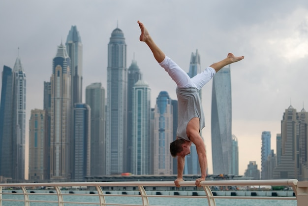 Muscular man doing workout on the street with cityscape of skyscrapers in dubai. concept of healthy lifestyle and modern.