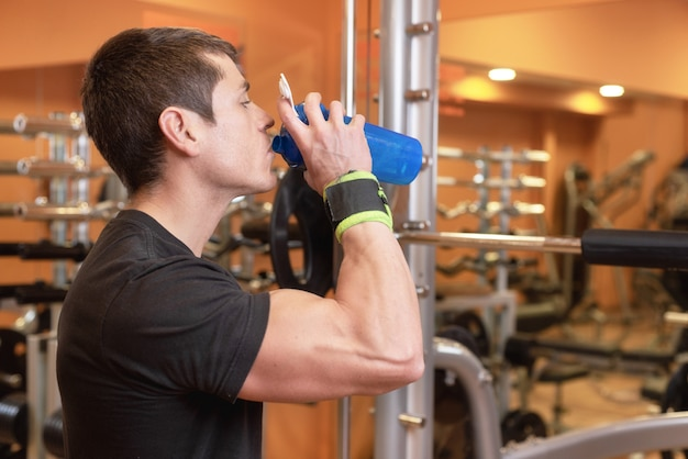 Muscular man drink water from blue bottle in the gym.
