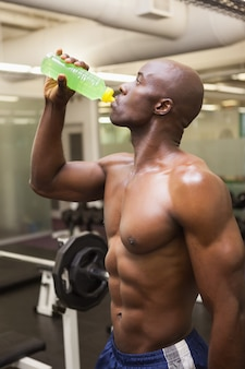Muscular man drinking energy drink in gym