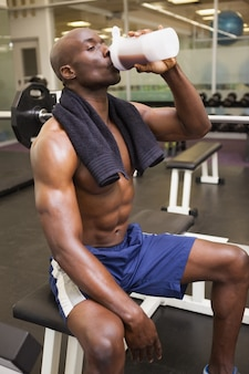 Muscular man drinking protein in gym