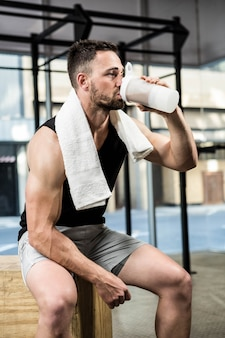 Muscular man drinking protein shake at the crossfit gym