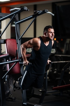 Muscular man during a workout at the gym trains the triceps on the parallel bars