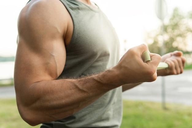 저항 고무 밴드 야외 운동하는 동안 근육 질의 남자.