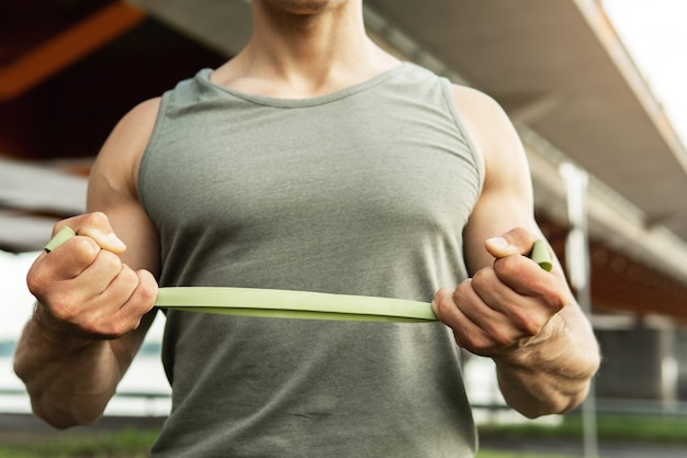 Muscular man during  workout with a resistance rubber bands outdoors.