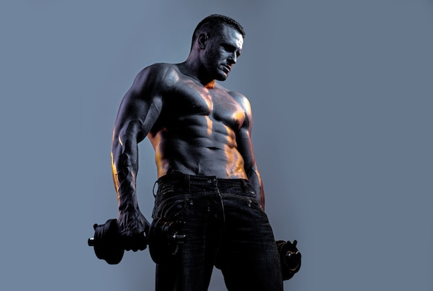 Muscular man exercises with dumbbell over neon black blue background.