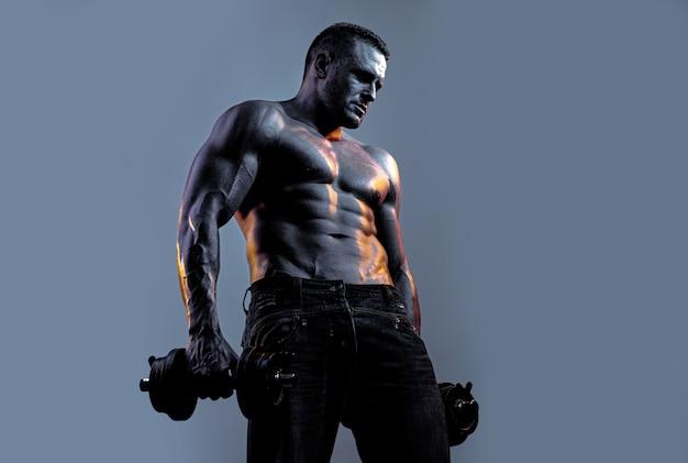 筋肉の男は、ネオンブラックブルーの背景の上にダンベルで運動します。