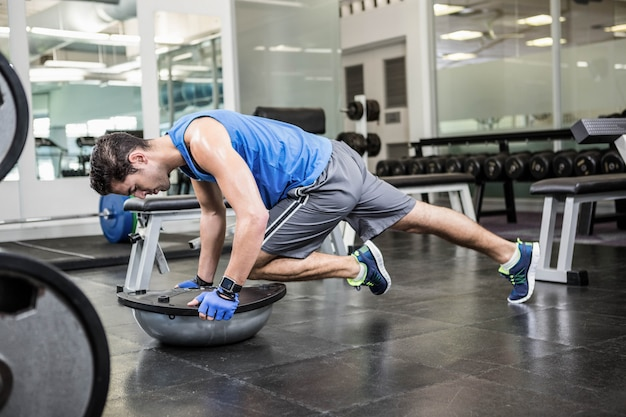 Muscular man exercising with bosu ball in the gym