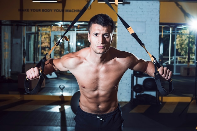 Muscular man exercising with fitness strap in gym