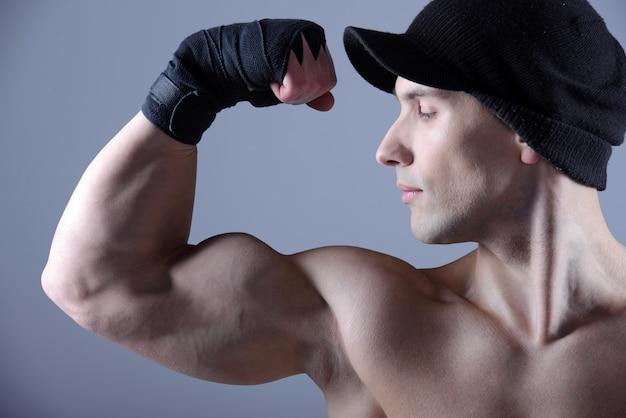 Muscular man flexing his biceps in studio.