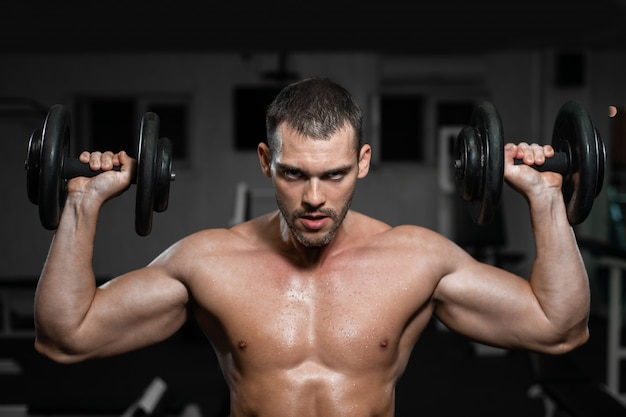 Muscular man in the gym training with dumbbells, guy pumps his deltoid muscle