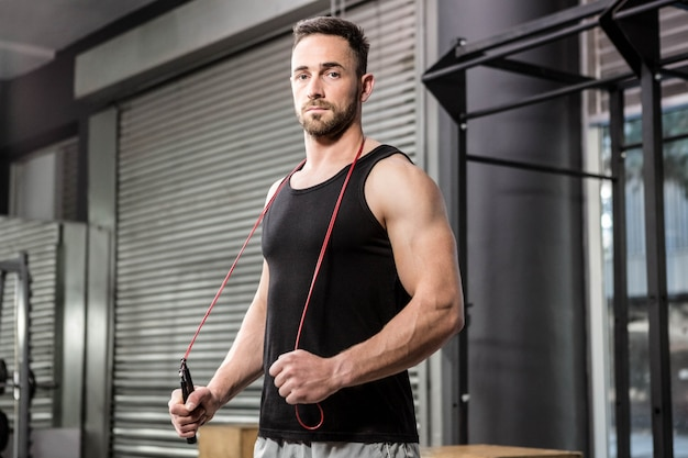 Muscular man holding rope around his neck at the crossfit gym