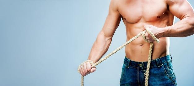 Мускулистый мужчина держит толстую веревку с копией пространства