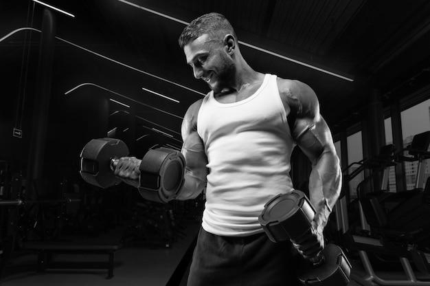 Мускулистый мужчина в белой футболке тренируется в спортзале с гантелями. прокачка бицепса. концепция фитнеса и бодибилдинга.