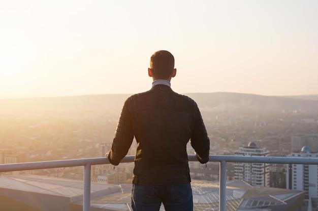 검은 재킷을 입은 근육질의 남자는 회색 금속 난간을 잡고 도시 경관과 언덕 실루엣 뒷면 전망을 감상하며 일출을 감상합니다.
