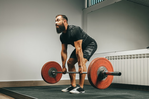ジムでバーベルを持ち上げる黒いスポーツウェアで筋肉の男