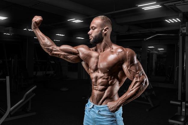 Мускулистый мужчина в джинсах позирует в тренажерном зале