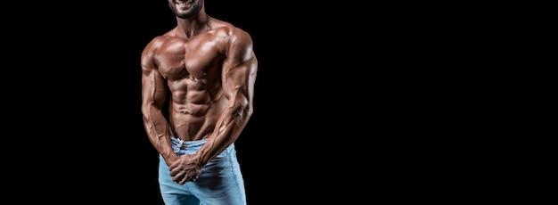 Мускулистый мужчина в джинсах позирует изолированным на черном