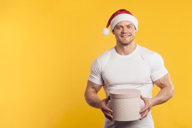 산타 클로스 모자와 흰 셔츠에 선물 상자에 근육 질의 남자, 고립 된 노란색 벽 위에 서