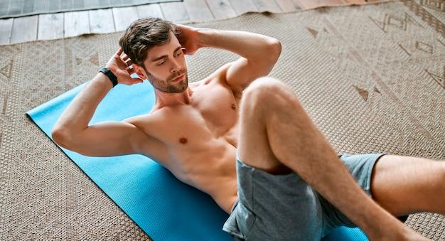Мускулистый мужчина в спортивных шортах делает тренировку дома в просторной гостиной. здоровый активный образ жизни, спорт, фитнес.