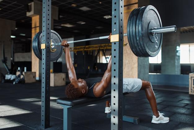 Мускулистый мужчина в спортивной одежде, упражнения со штангой на тренировке в тренажерном зале.