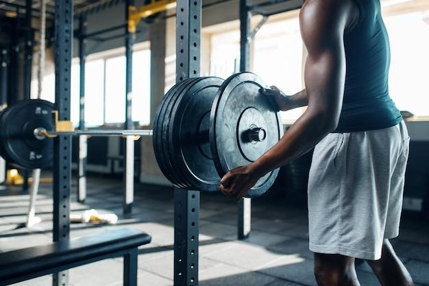 Мускулистый мужчина в спортивной одежде готовит штангу на тренировке в тренажерном зале.