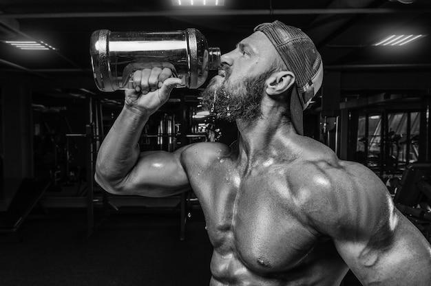 Мускулистый мужчина в тренажерном зале пьет из огромной бутылки. концепция фитнеса и бодибилдинга.