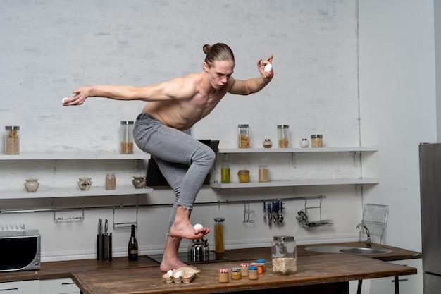 Мускулистый мужчина на кухне, балансируя яйца.