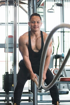 Muscular man is doing battle rope exercise