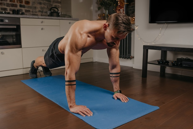 A muscular man is doing pushups on a blue yoga mat in his apartment