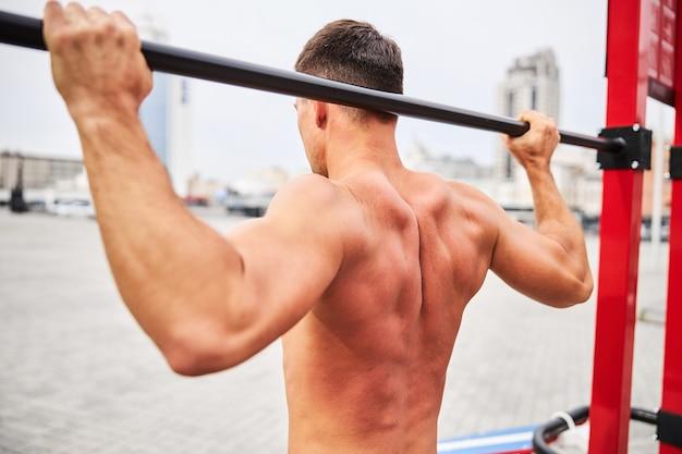 筋肉質の男が市内中心部のスポーツグラウンドでクロスバーを引き上げながら背中を運動している