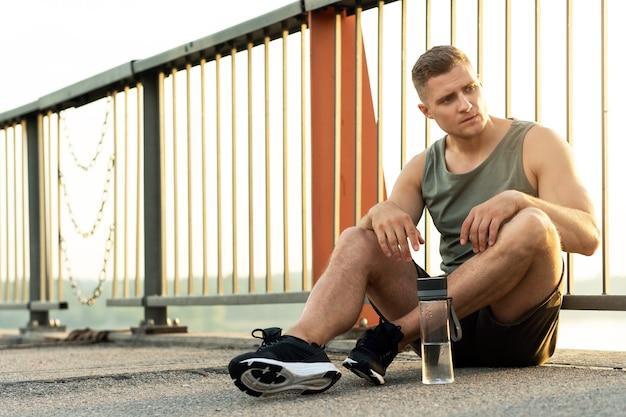 Мускулистый мужчина отдыхает после тренировки на улице города