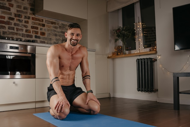 A muscular man is sitting on a blue yoga mat in his apartment