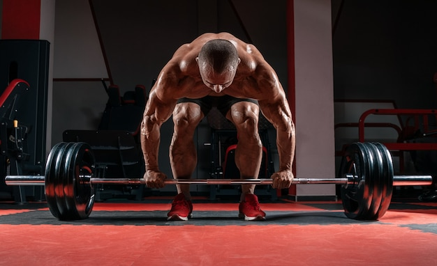 Muscular man is unbending with a barbell in his hands. deadlift. bodybuilding and powerlifting concept.