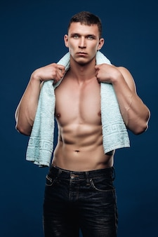 Muscular man in jeans with a naked torso, cubes, holding the towel around neck after a workout. sports portrait in studio on a blue background.