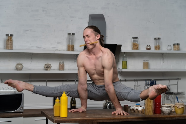 Muscular man keep balance on the hands in the kitchen and holding pasta in the mouth concept creativ...