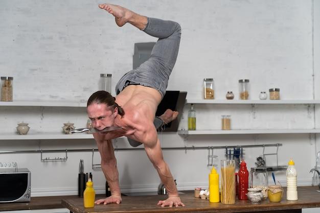 Мускулистый мужчина держит равновесие на руках на кухне и держит нож во рту