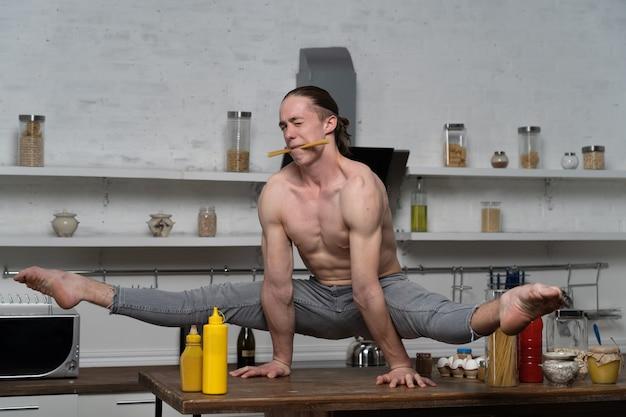 Мускулистый мужчина держит равновесие на руках на кухне и держит во рту макароны. концепция творчества на кухне и здорового образа жизни.