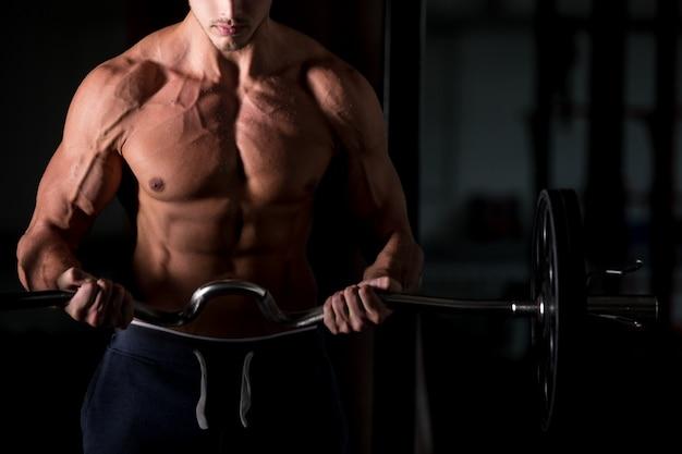 헬스 클럽에서 바 벨을 드는 근육 남자