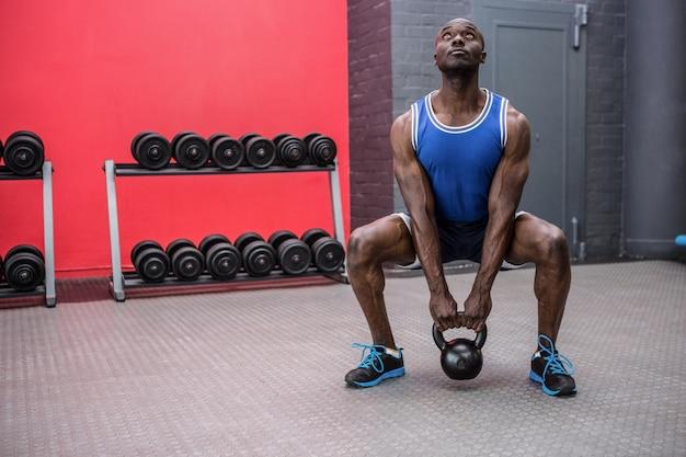 ケトルベルを持ち上げる筋肉の男