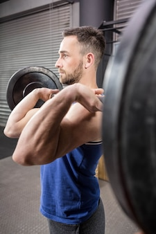 Muscular man lifting barbell at the crossfit gym