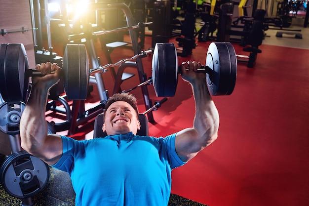근육 질의 남자는 체육관에서 아령 리프트