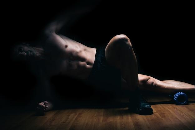 ストレッチ体操をしている床に横たわっている筋肉の男