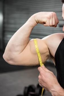 Muscular man measuring biceps at the crossfit gym