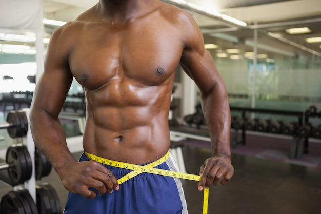 Muscular man measuring waist in gym