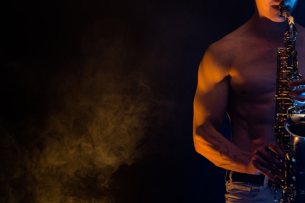 Мускулистый мужчина с обнаженным торсом играет на саксофоне с дымчатым красочным фоном