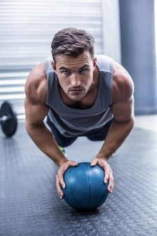 Muscular man on a plank position with a ball